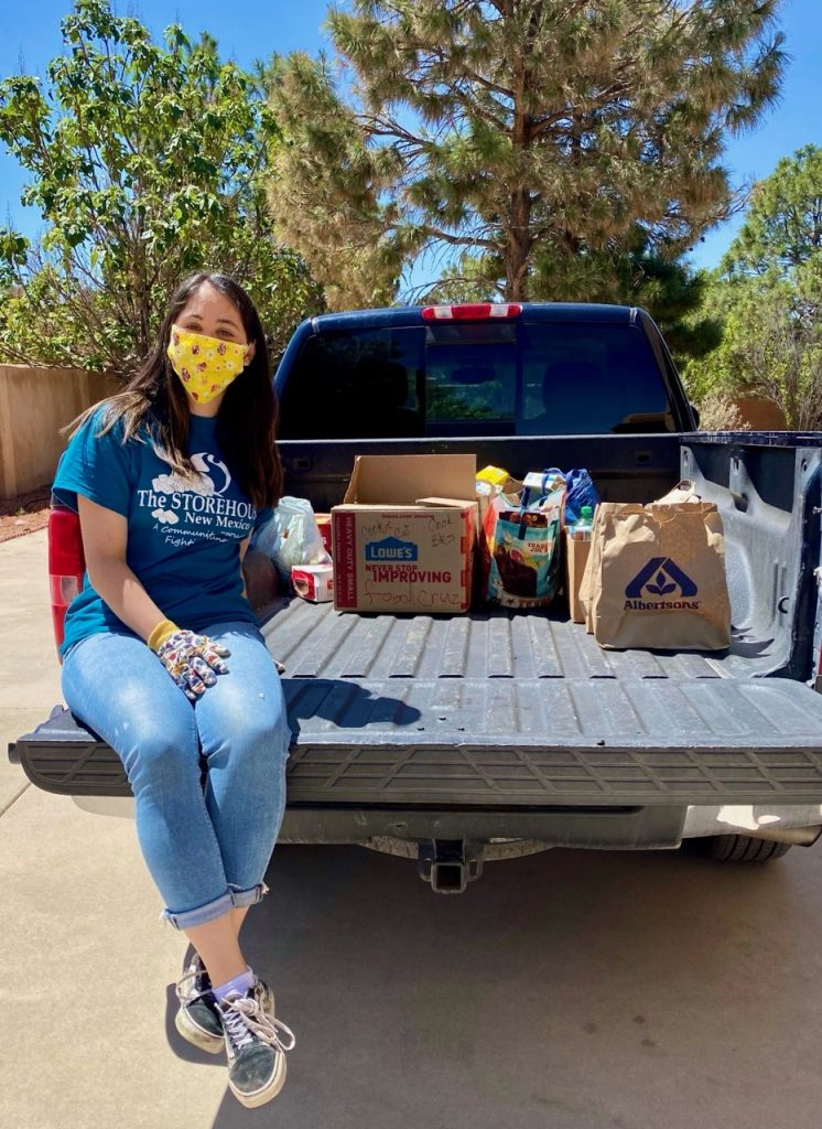 Izzy sits on a truck with some of her Grub Crawl food donations. She is wearing a mask and gloves due to Coronavirus, and is smiling for the camera.