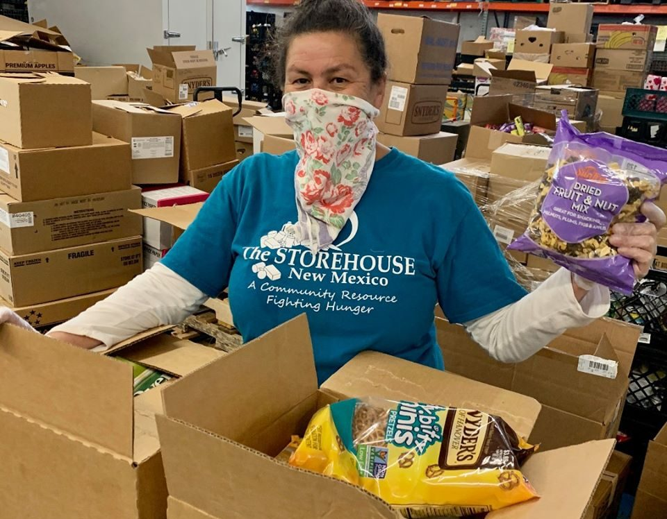 This wonderful volunteer is helping pack up boxes. She is wearing a scarf over her nose and mouth.