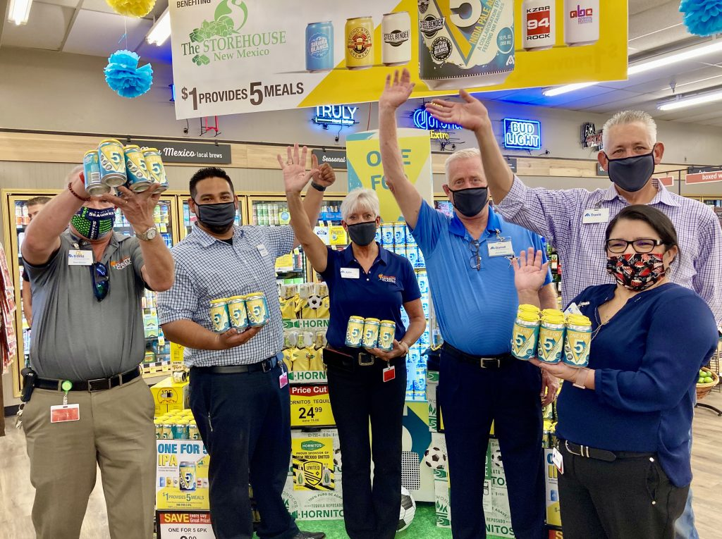 Albertsons Market managers and directors hold cans of One for 5 beer that they are selling as a fundraiser for the Storehouse.