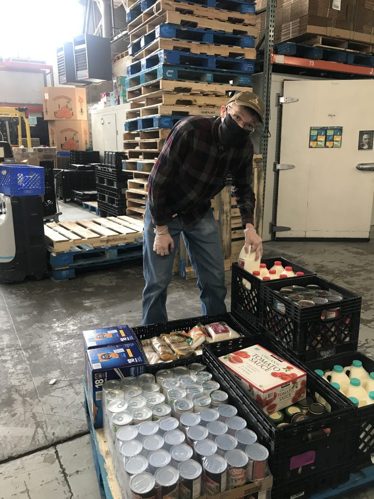 Elder Hunt helps pack food for clients at the Storehouse. He volunteers several times a week as part of his service mission with the Church of Jesus Christ of Latter-day Saints
