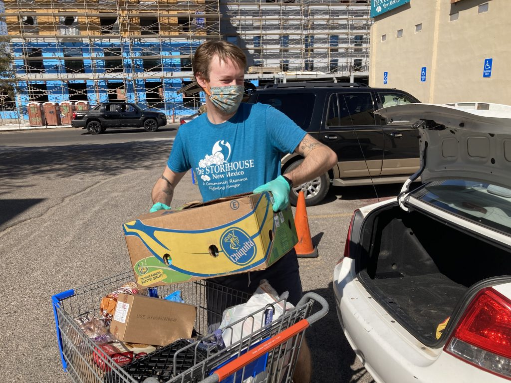 A Storehouse employee loads food up in a car for a family. When you donate to our food panty, you help feed our neighbors.