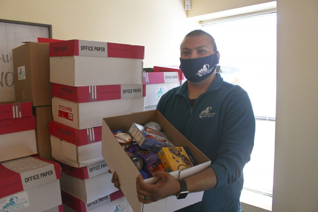 Staff Member Tim holds a box of food for a family. He is wearing a mask. Our local churches helped with staffing by raising money for Tim's salary!