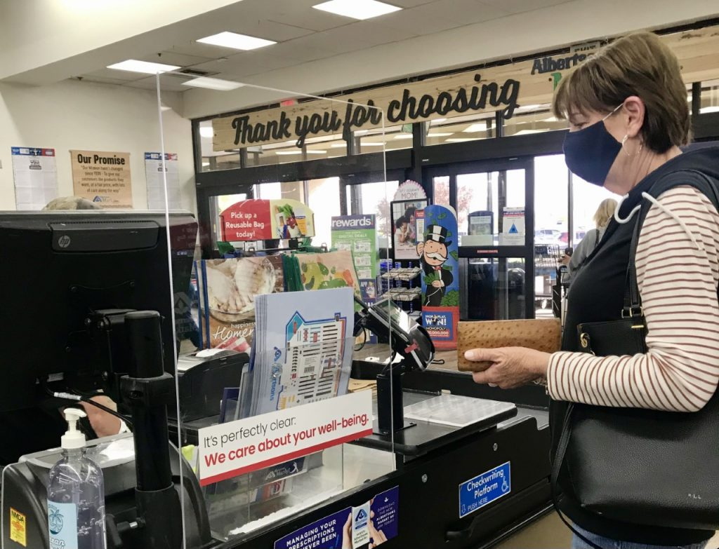 woman pays at the Albertsons Market checkout