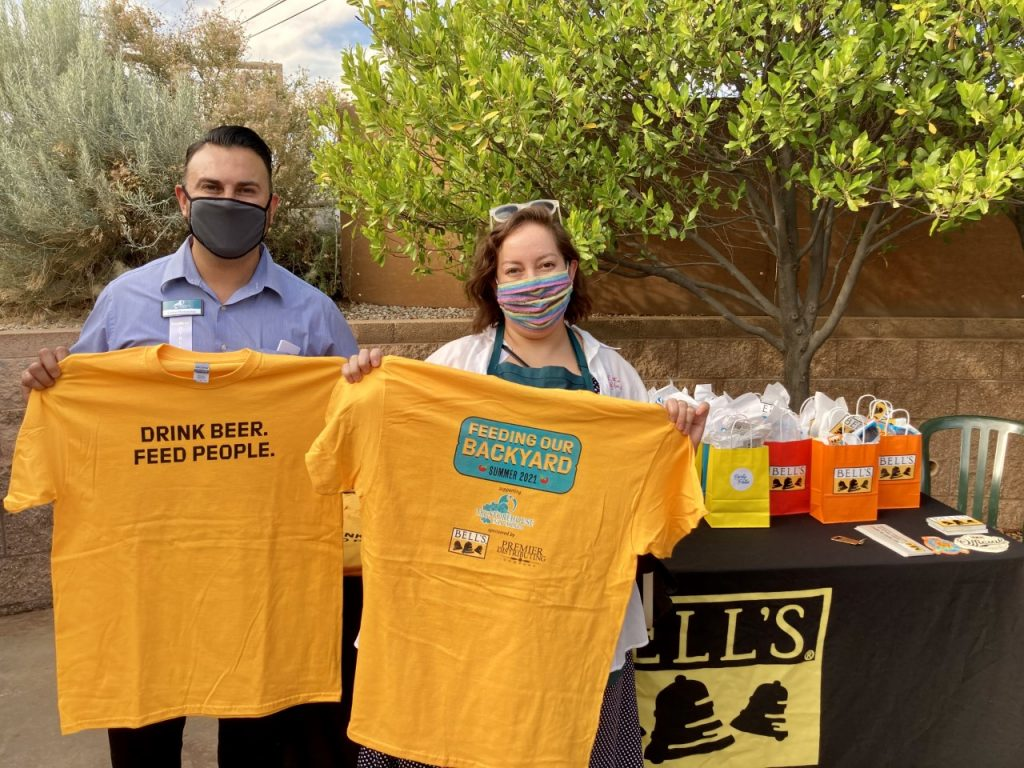 Storehouse board member and staff holding Feeding Our Backyard t-shirts
