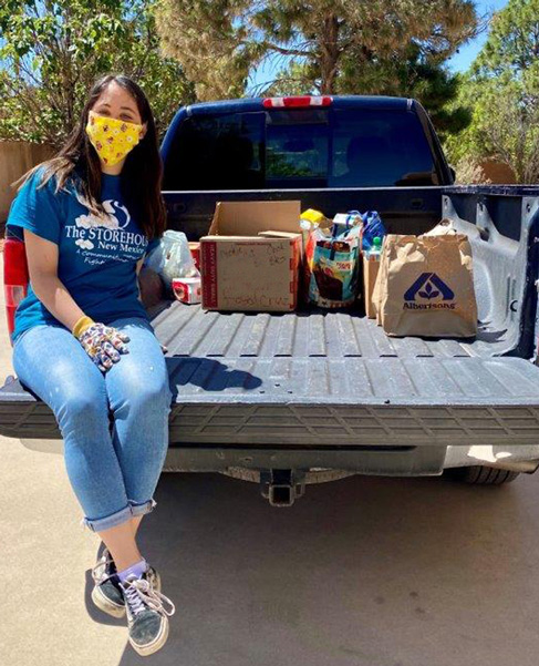 Izzy Thomas sits in the bed of the pick up truck she uses to pick up donations during the Grub Crawl food drive for the Storehouse food bank.