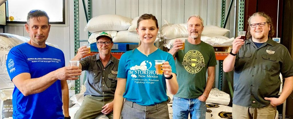 Brewers from Sierra Blanca Brewing Company, Steel Bender Brewyard, and Second Street Brewery toast the new One for 5 hazy pale ale beer they brewed together to raise money for the Storehouse of New Mexico.