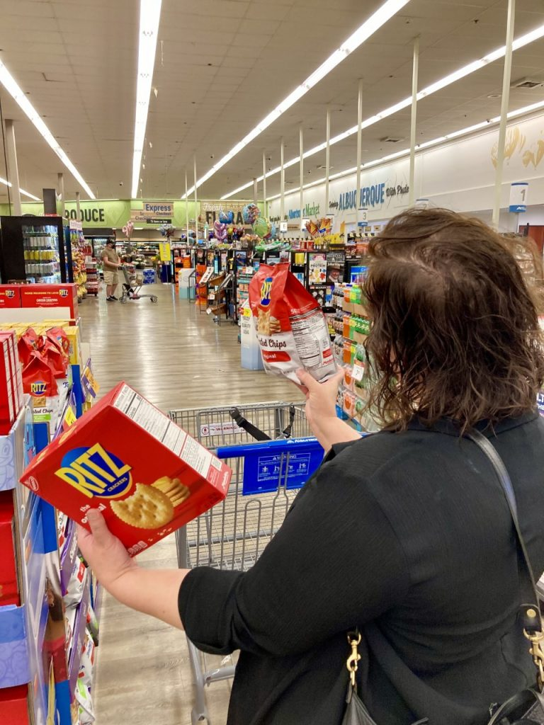 a woman comparing two kinds of crackers to save money on her grocery bill